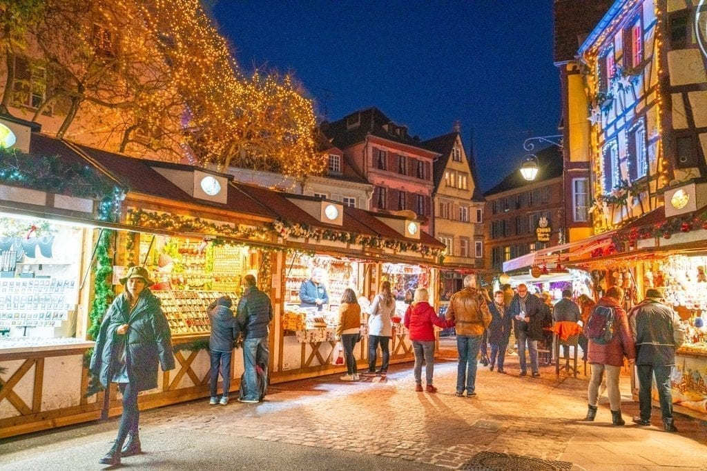 Colmar Christmas market at night with shoppers in front of several stalls