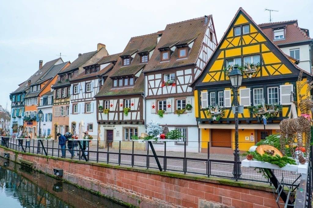 Row of houses in La Petite Venise with a yellow house the most prominent. Located in Colmar France