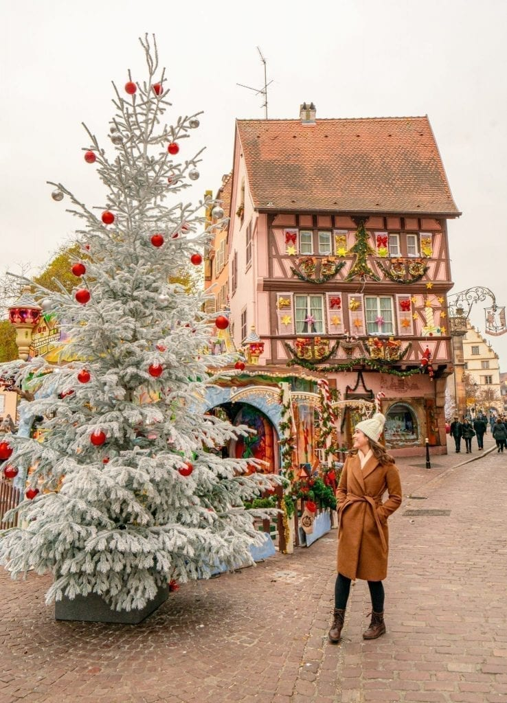 Kate Storm in a brown coat standing with a white Christmas tree in Colmar. A decorated pink house is in the background--this is a classic photo spot in Colmar in winter!
