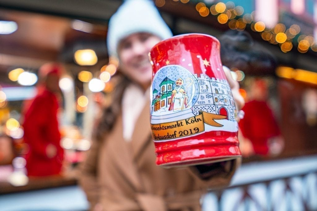 Kate Storm holding a red mug out to the camera at a Cologne Christmas market, home to some of the best Christmas markets in Europe