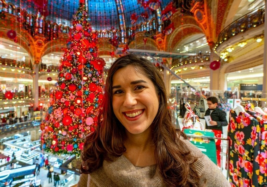 Kate Storm in a brown sweater in front of the 2019 Galeries Lafayette Christmas tree in Paris