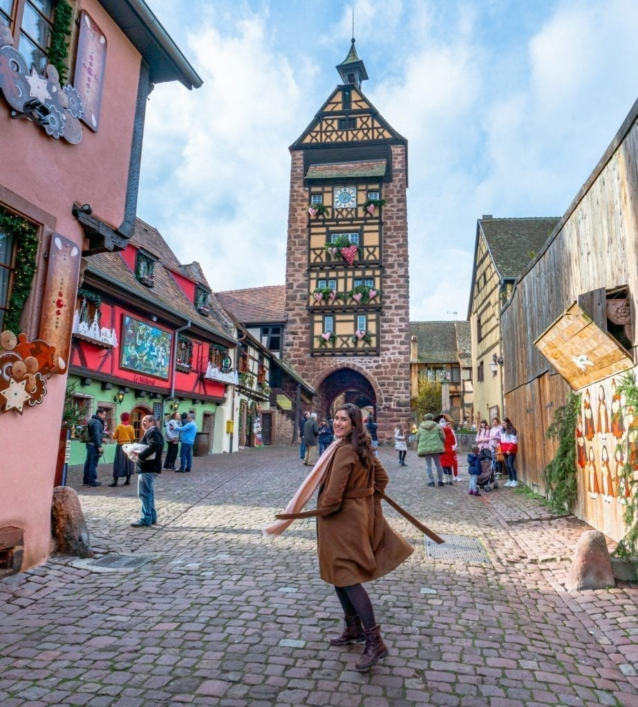 Kate Storm spinning in front of a clock tower in Riquewihr, one of the best day trips in Alsace!
