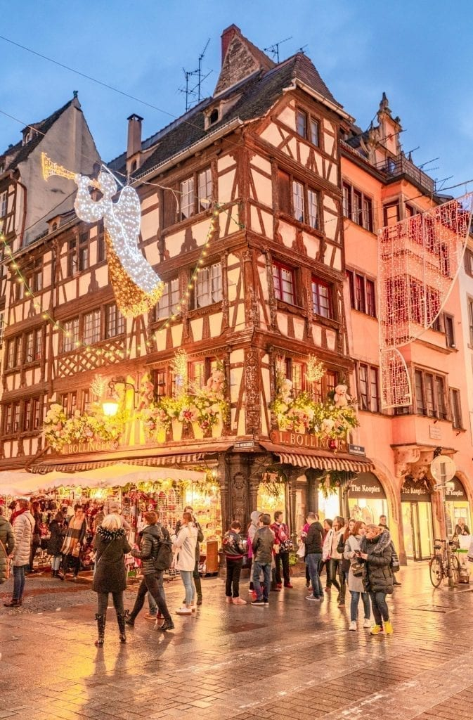 Crowd of people crossing the street in Strasbourg in December in front of a beautiful half-timbered house with Christmas lights