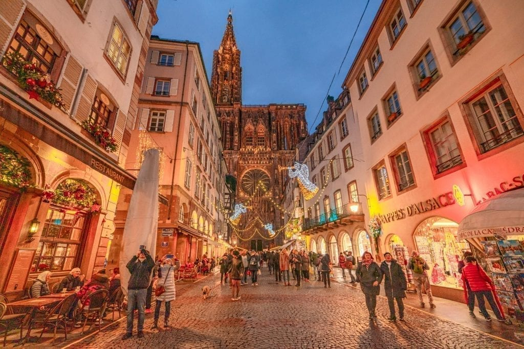 Street in Strasbourg France decorated for Christmas at blue hour, with the Strasbourg Cathedral in the background