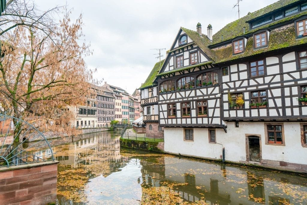 La Petite France neighborhood in Strasbourg France with a half-timbered house on the right and a canal on the left