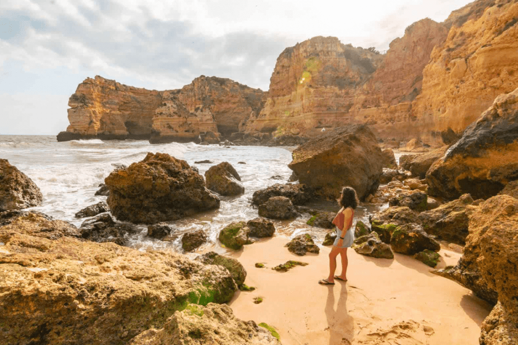 Woman standing on a rocky beach on the Algarve Coast, one of the best road trips in Europe