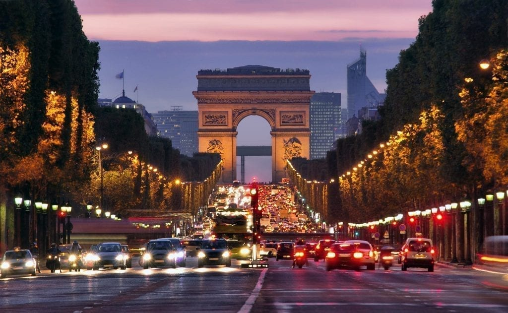Champs Elysses during the evening in Paris, with traffic in front, Arc de Triomphe in the rear of the photos, and a slight pink sunset visible.