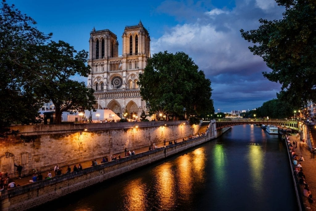 Seine River in Paris at night with Notre Dame visible on the left. Strolling along the Seine is one of the most classic things to do in Paris at night.
