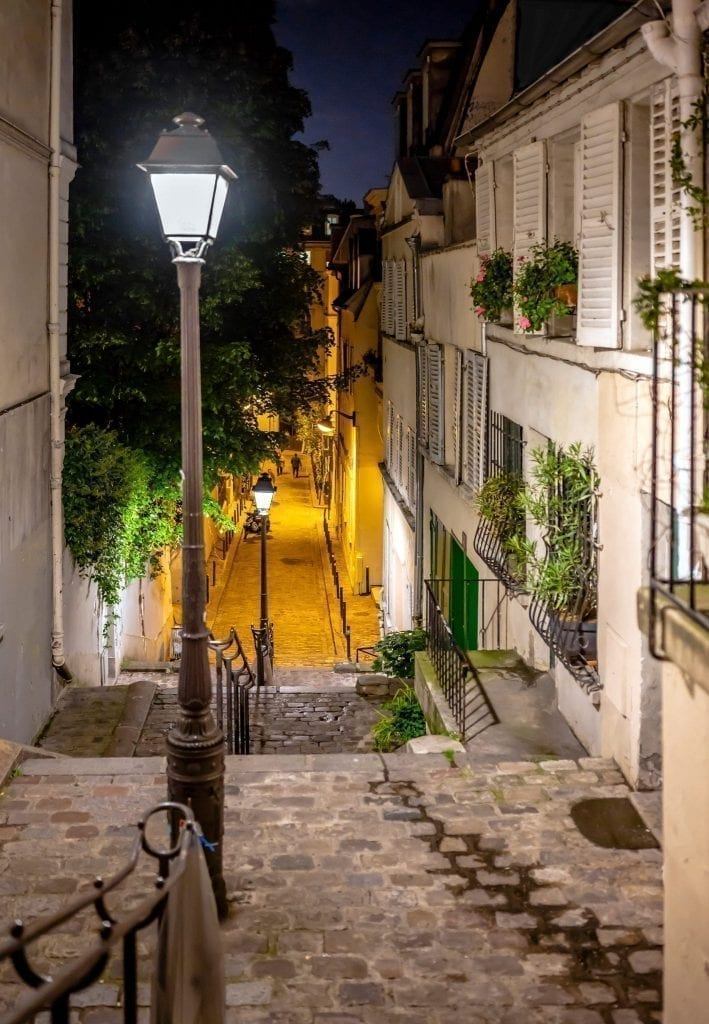 street in Montmartre in Paris at night with a streetlight to the left. Montmartre is a great neighborhood to spend an evening in Paris