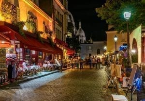 Montmartre street scene with cafes to the left. Montmartre is one of the best neighborhoods to visit when deciding what to do in Paris at night