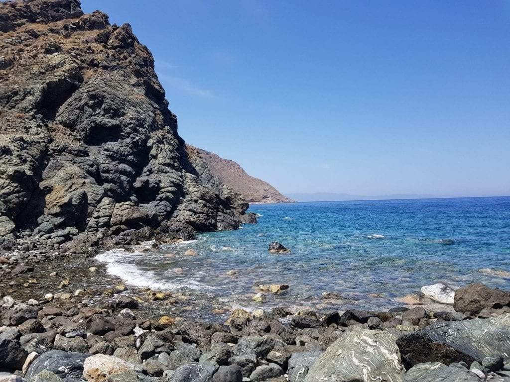 Volcanic beach in eastern Crete with bright blue water and black, rocky sand