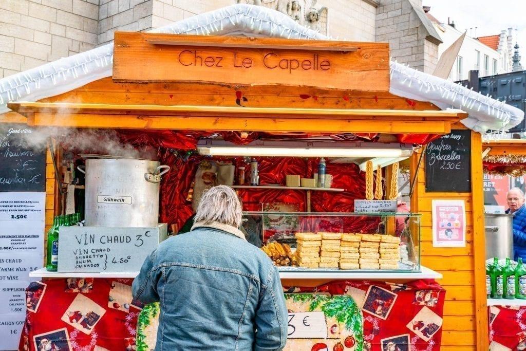 man buying gluhwein at belgium christmas market