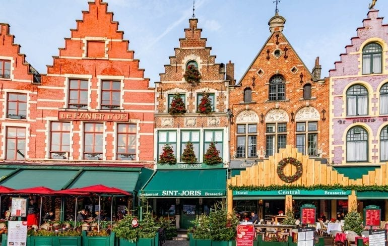 Grote Markt in Bruges Belgium with 4 colorful buildings visible with green awnings out front--an essential stop during your 3 day Belgium itinerary