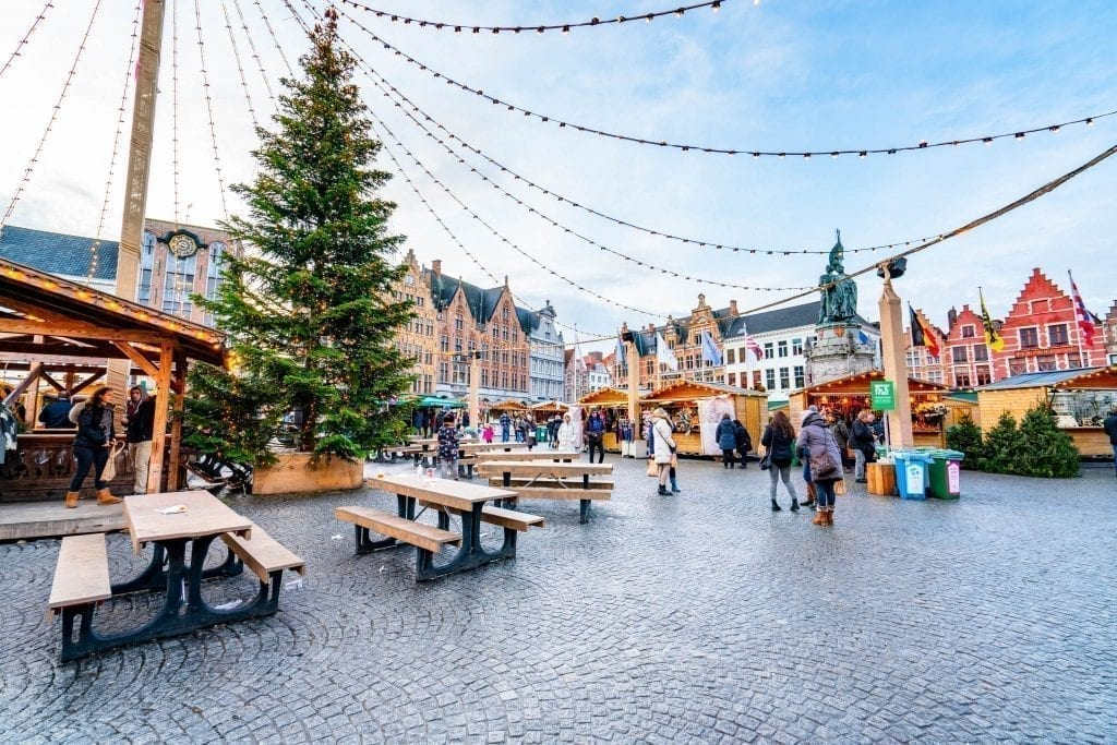 One of the best Christmas markets in Europe in Bruges Belgiu with a large tree on the left side of the photo