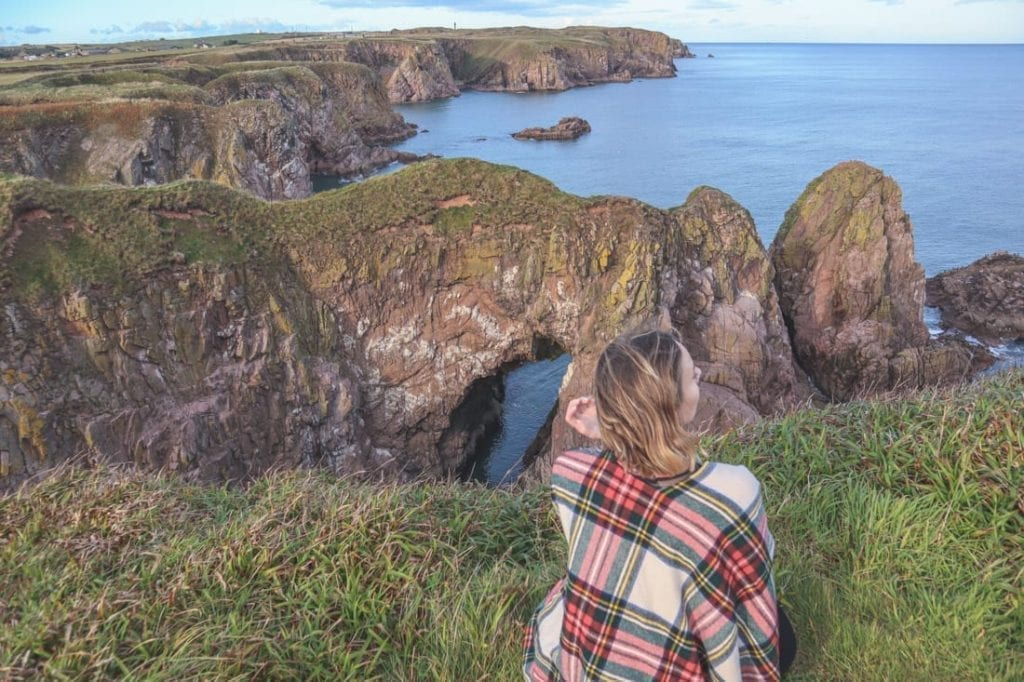 Gemma Armit wearing tartan and looking out over a cliff on the east coast of Scotland