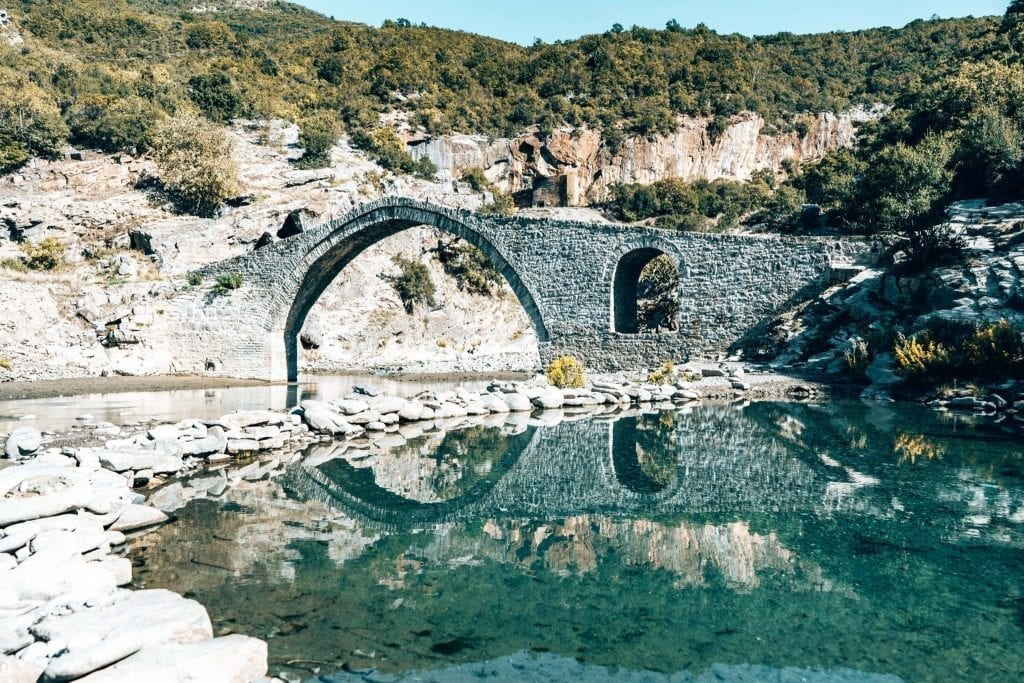 Stone footbridge built over a bright blue river, as seen on an Albanian road trip