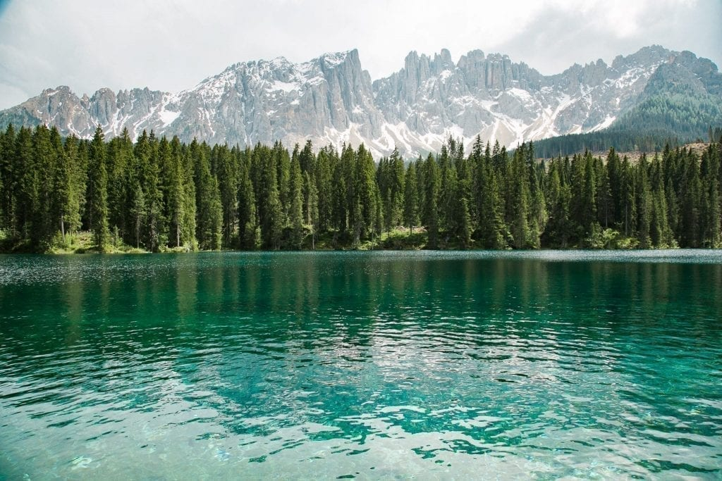 Photo of Italian Dolomites on a cloudy day with a bright lake in the foreground. The Italian Dolomites are one of the best additions to a Europe road trip itinerary!