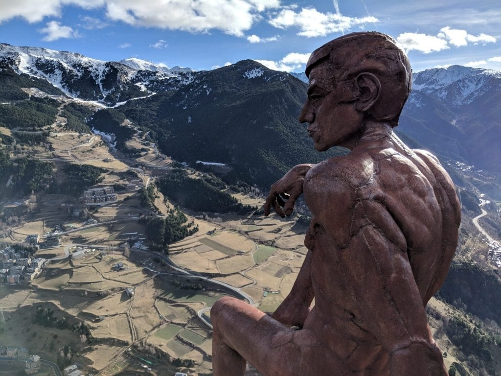 Bronze statue of a man overlooking a vista with mountains in the background on one of the shortest, prettiest road trips in Europe: from Barcelona to Andorra