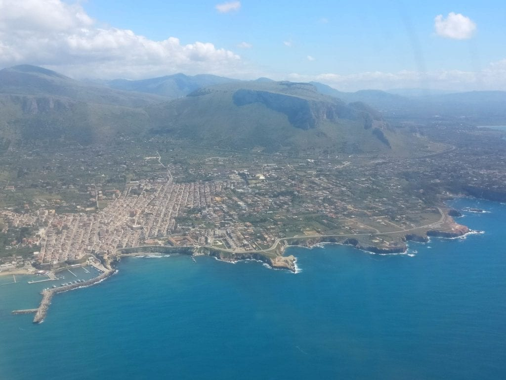 View of Sicily with the Meditteranean Sea in the foreground, taken from a plane window