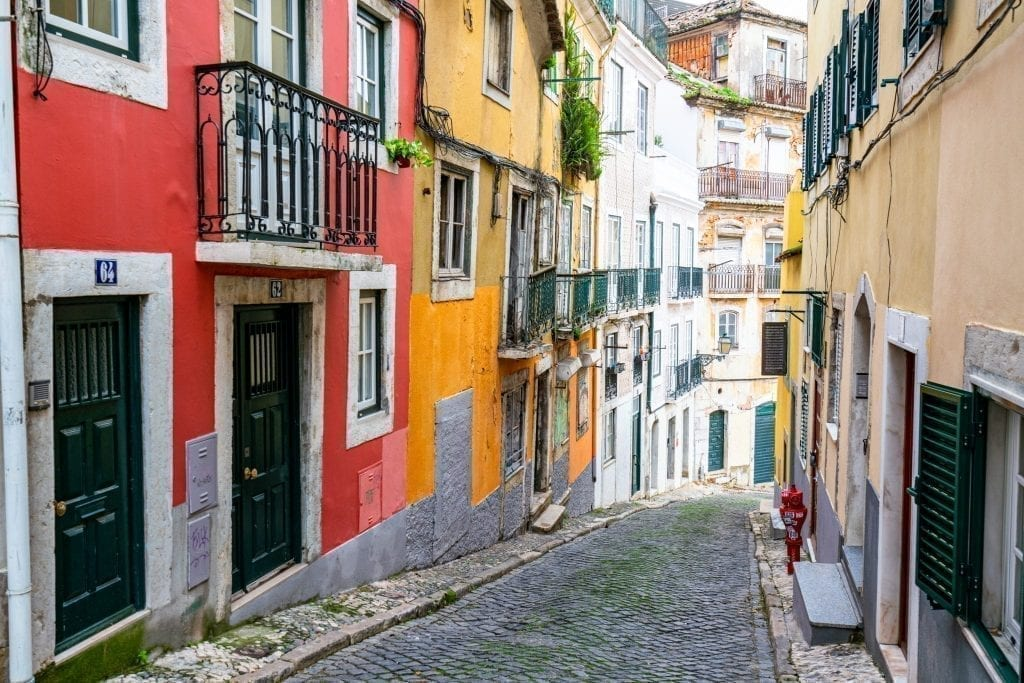 Colorful street in Lisbon Portugal with red and yellow buildings on the left