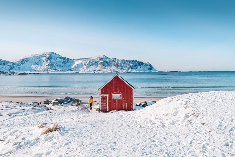 Snowy beach in Lofoten Norway as seen during a northern Europe road trip, with a small red building in the center of the photo