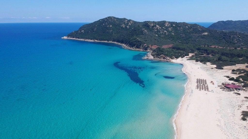 White sand beach of Sardinia as seen from above when driving through Sardinia, with turquoise water visible on the left side of the photo.