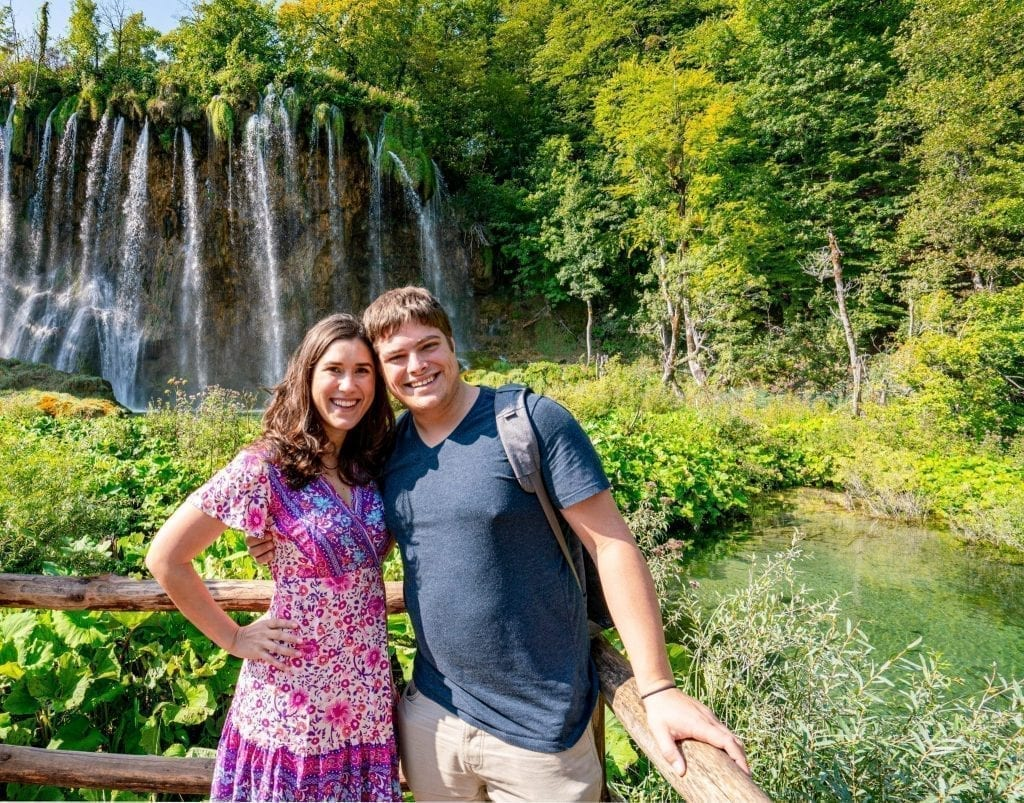Kate Storm and Jeremy Storm standing in front of a waterfall when visiting Plitvice Lakes National Park Croatia