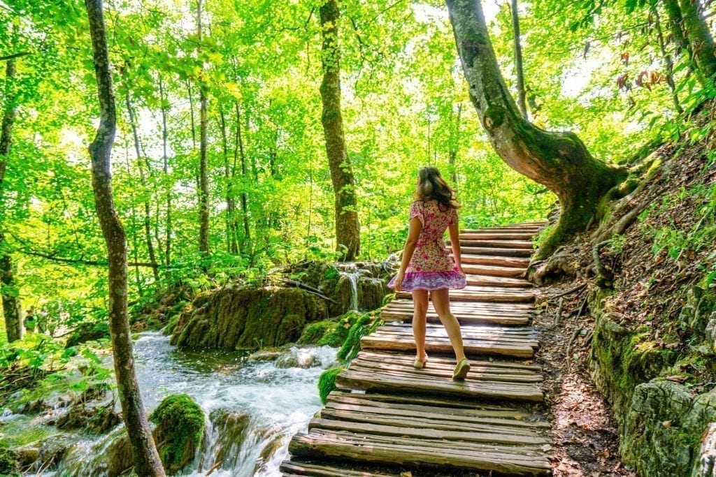 Kate Storm in a pink dress twirling on a boardwalk when visiting Plitvice Lakes Croatia. Trees surround the boardwalk and water is running under it.
