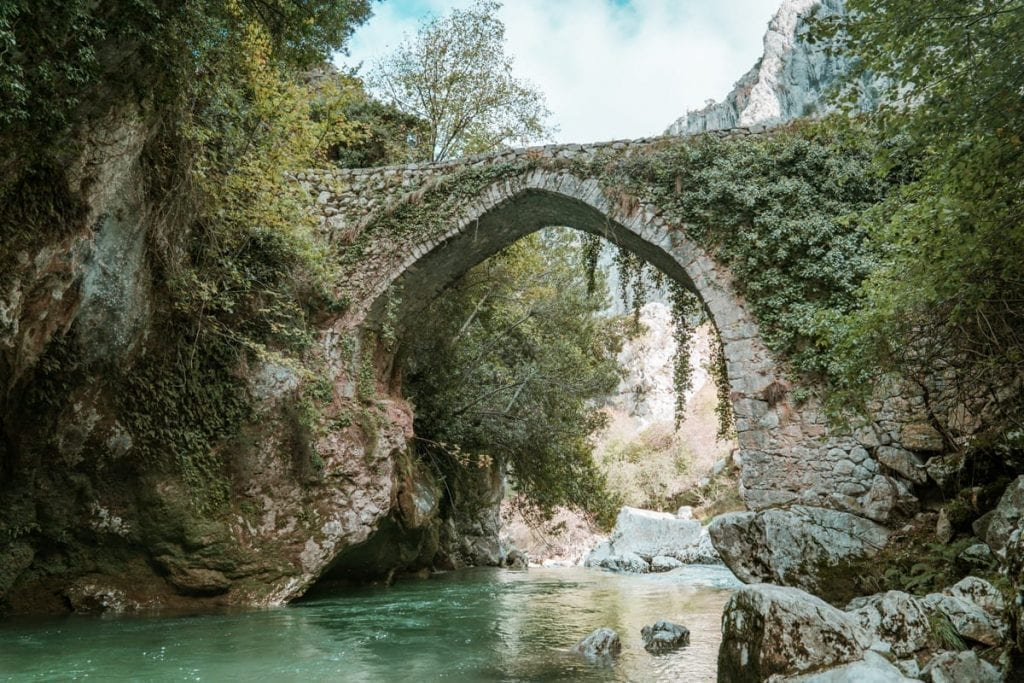 Spain Picos de Europa Puente la Jaya stone bridge over a bright blue river