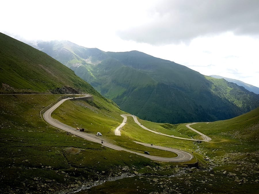 Transfăgărășan road winding through the mountains of Romania on a cloudy day--definitely not the easiest road trip in Europe as far as driving goes!