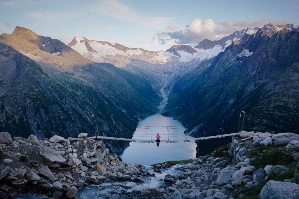 Person sitting on a small footbridge in Zillertal Alps in Austria, with a lake and mountain range visible in the distance