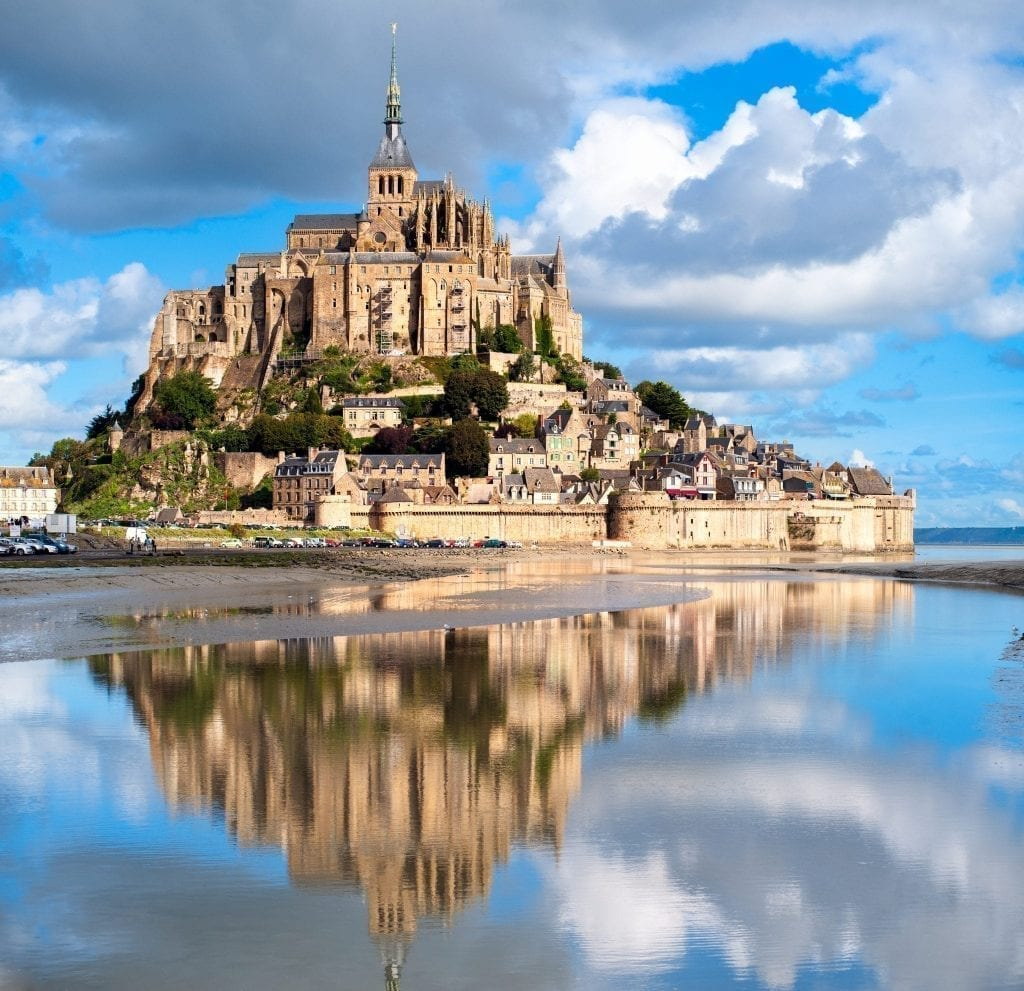 Mont St. Michel in northern France with its reflection showing in the water in the bottom half of the photo