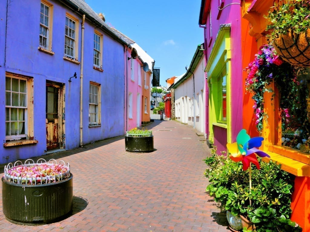Brightly colored street in Kinsale Ireland with a purple building in the left foreground and a red building on the right foreground. Kinsale is one of the prettiest small towns in Ireland.