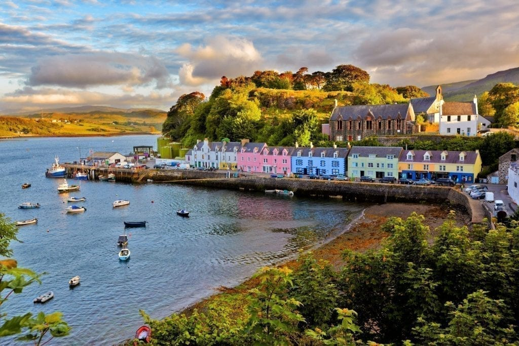 Colorful village set along the water on the Isle of Skye in Scotland with boats parked in the harbor--Scotland is home to some of the best Europe itinerary road trip options around!
