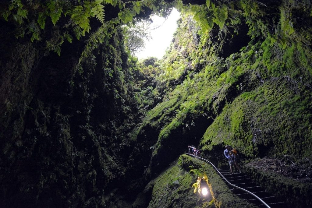 Cave on Terceira Island in the Azores with light shnging in an opening at the top and a trail visible on the right.