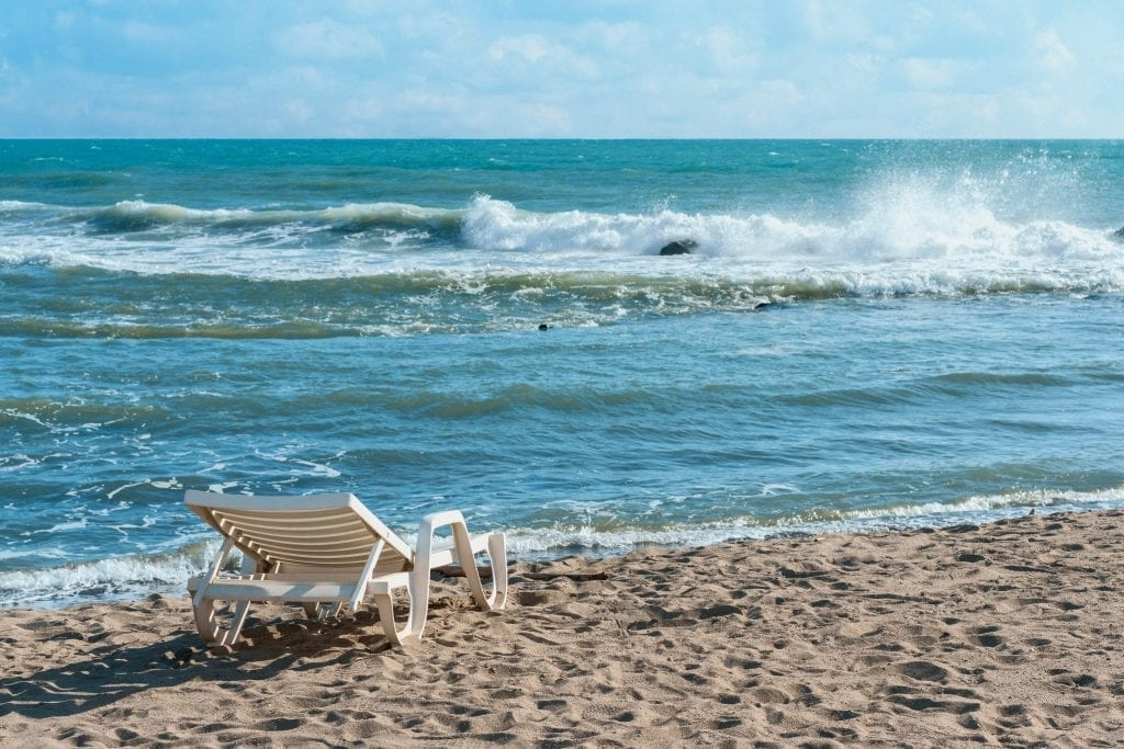 White deck chair on the edge of Ostia Lido beach with the sea and one crashing wave taking up most of the photo