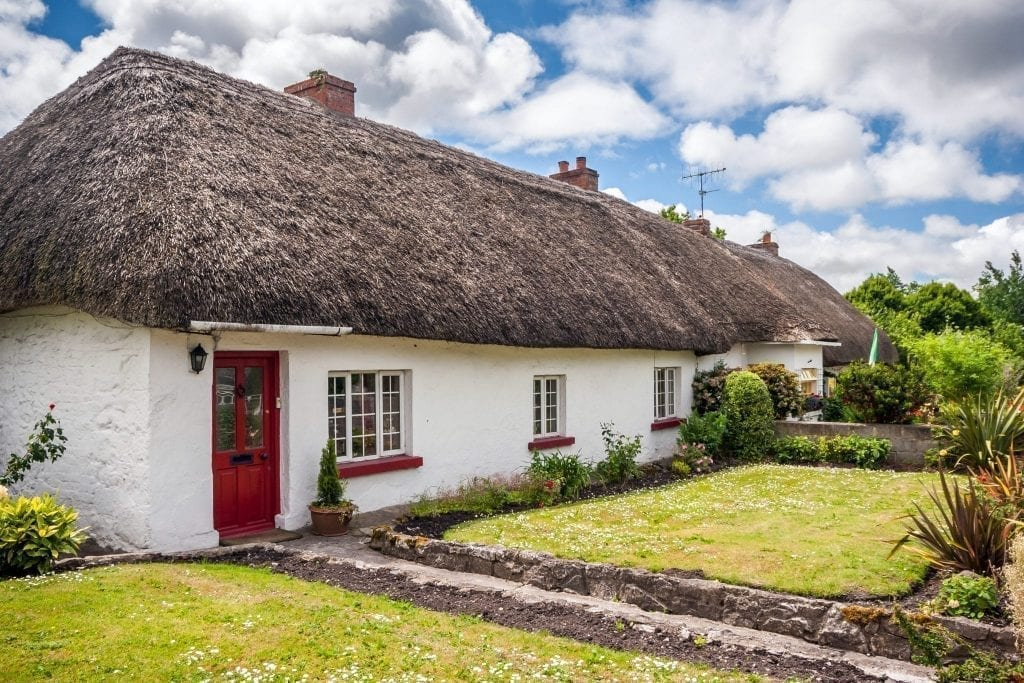 Thatched roof cottages in Adare Ireland with white walls and a red door. Adare is one of the best small towns in Ireland