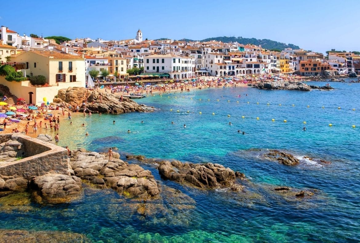 coastline of Costa Brava Spain as seen from across with water, with a village visible in the distance. Spain's Costa Brava is one of the best European road trip routes!