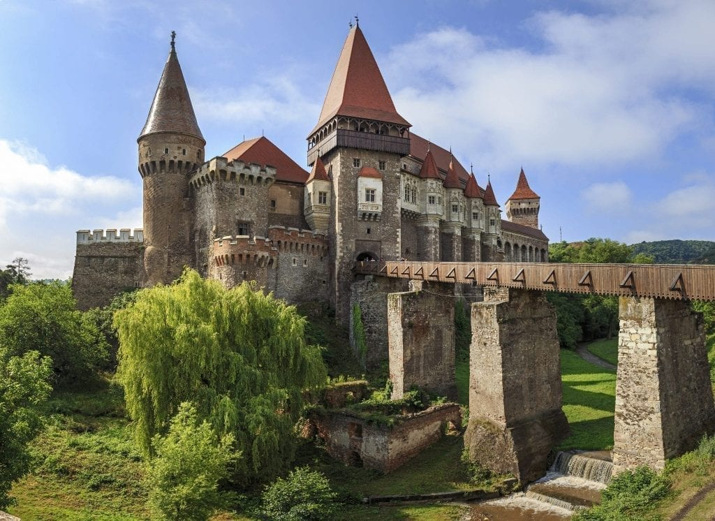 Corvin Castle in Transylvania with a bridge to the right side. Transylvania is one of the best road trips in Europe