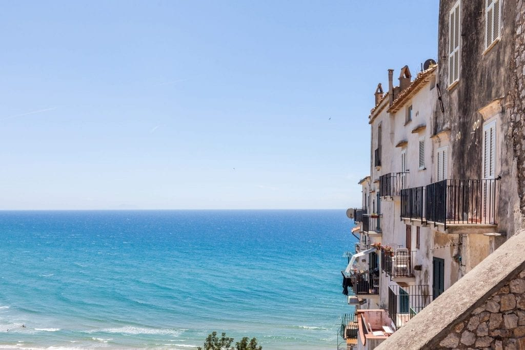 View of Sperlonga Italy, one of the most fun day tours from Rome Italy, with the town visible on the right and the bright blue water of the sea taking up most of the photo