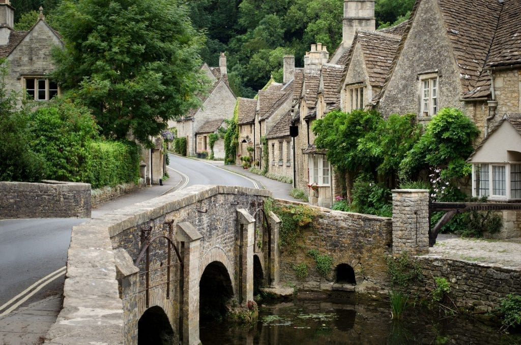 Castle Combe village in the Cotswolds with a small stone bridge in the foreground and stone houses in the background