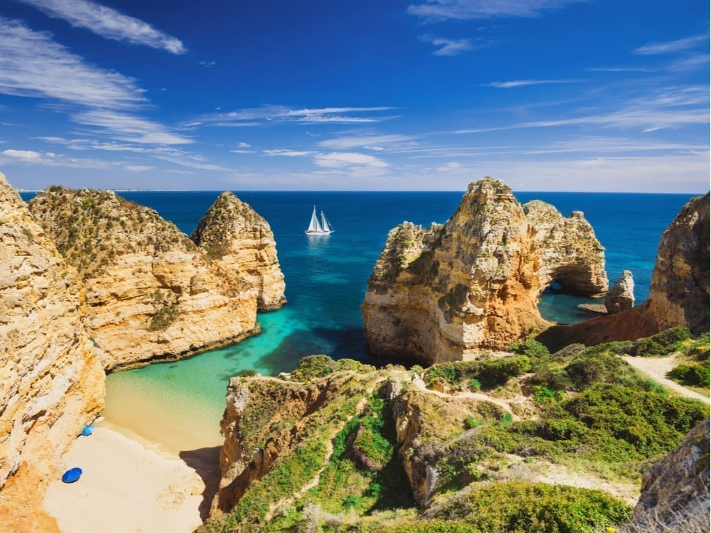View of small beach on Algarve Coast in Portugal with a sailboat in the distance and rocky cliffs jutting out to sea