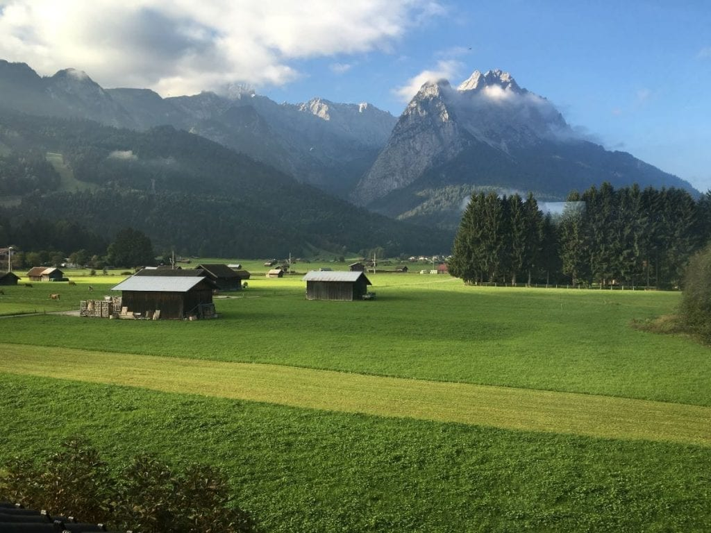 Garmisch Germany, expansive green field with a few houses framed by mountains in the background