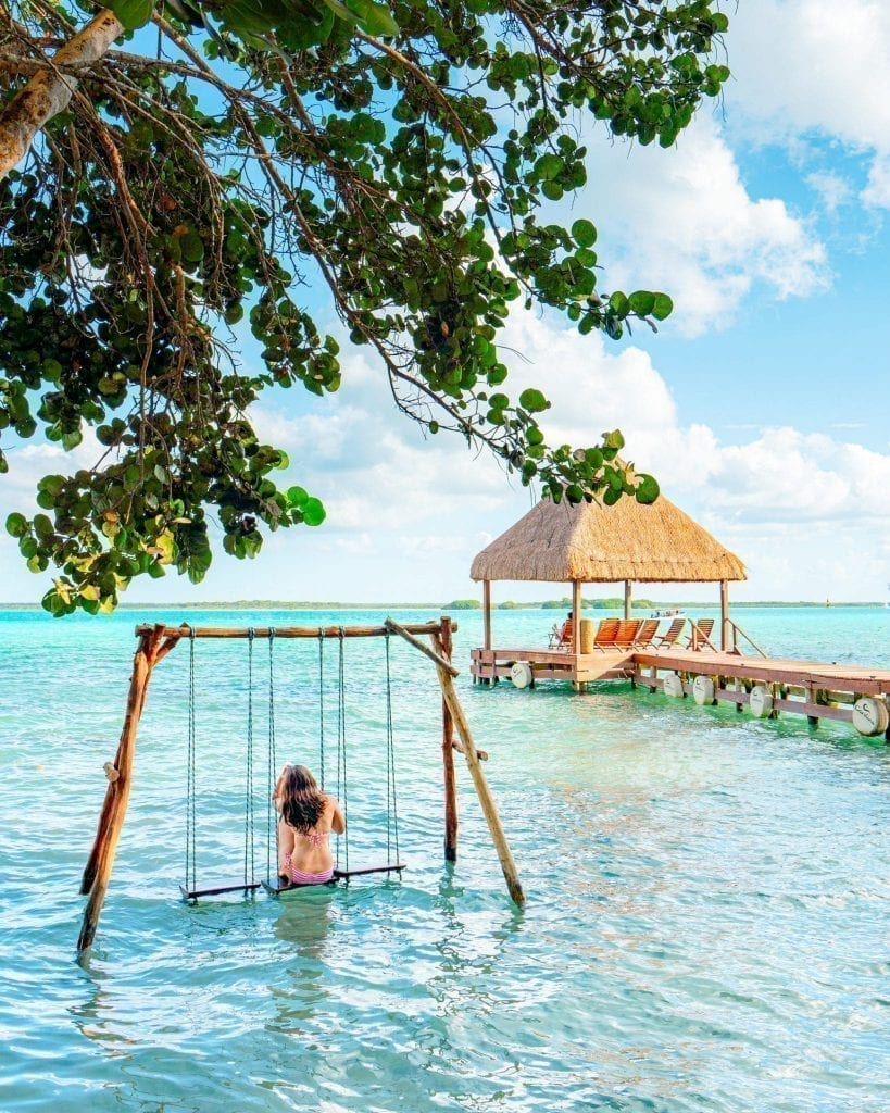 Kate Storm sitting on a swing in the water in Bacalar Mexico wearing a pink bikini--plenty of bathing suits definitely belong on your beach vacation packing list
