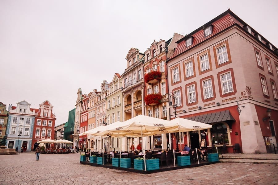 Colorful street in Poznan Poland with cafe visible in the foreground. Poznan is a great destination for those looking to explore Europe off the beaten path