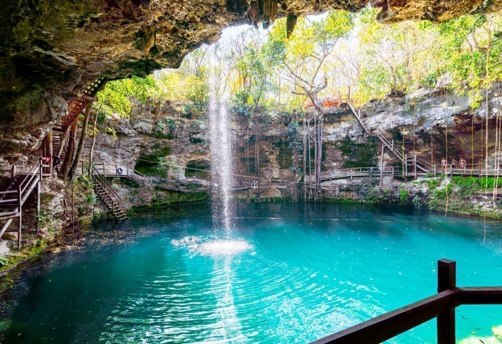 Cenote X'canche as seen from the interior of the small cave. Also known as the ek balam cenote. A waterfall is in the left side of the photo and the water is turquoise