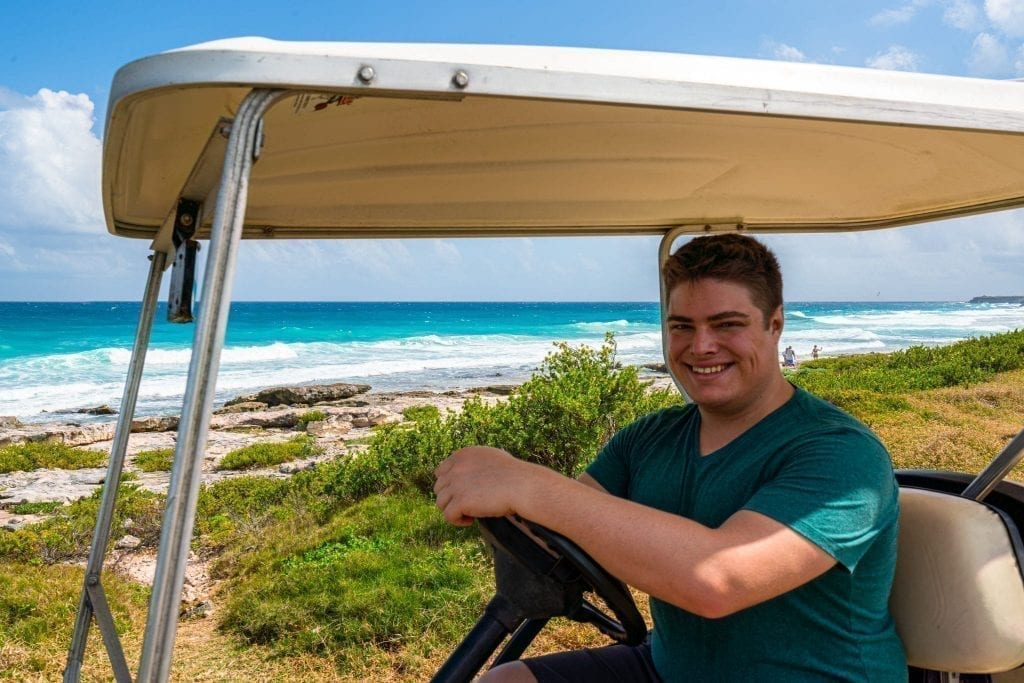Jeremy Storm in a green shirt sitting behind the wheel of a golf cart with the east coast of Isla Mujeres in the background. Renting a golf cart is one of the best things to do in Isla Mujeres