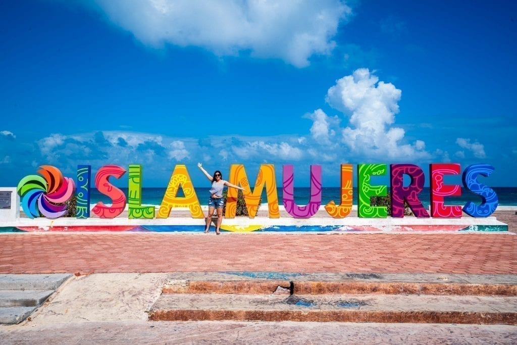 Kate Storm standing in front of colorful Isla Mujeres sign, one of the fun places to visit in Isla Mujeres Mexico
