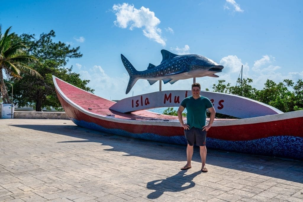 Jeremy Storm standing in front of Isla Mujeres sign with a whale shark on top of it