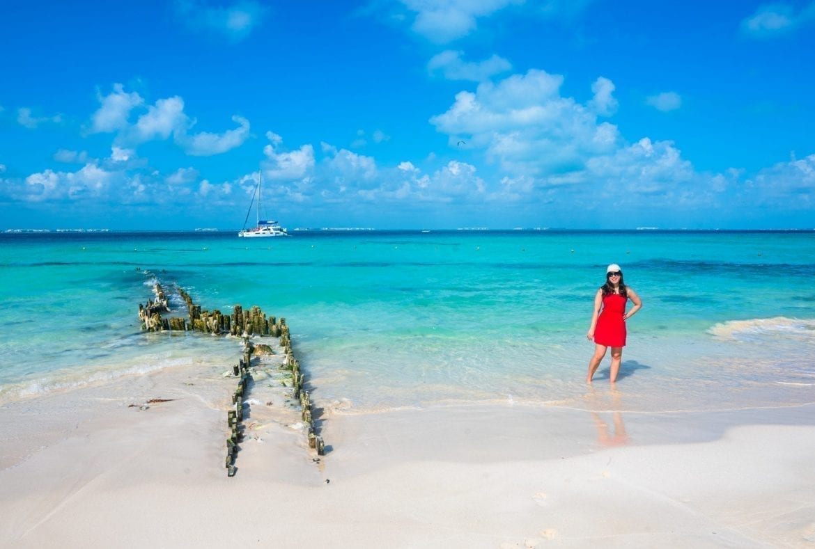 Kate Storm in a red dress standing on Playa Norte in Isla Mujeres. The remains of a dock are to her left.